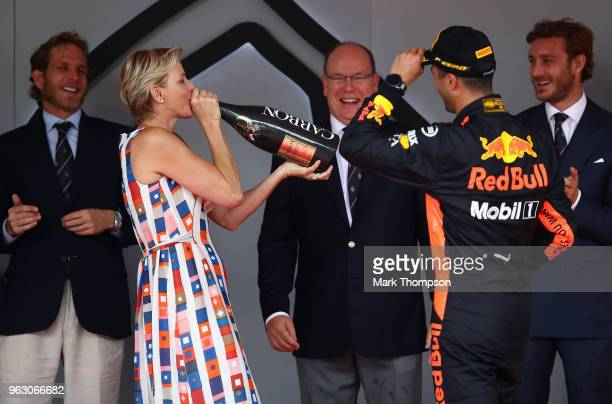Race winner Daniel Ricciardo of Australia and Red Bull Racing shares his champagne with Princess Charlene of Monaco on the podium during the Monaco...
