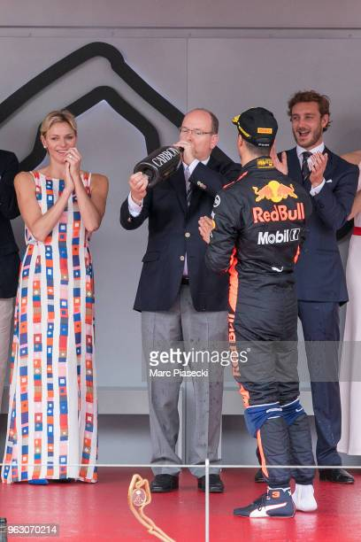 Race winner Daniel Ricciardo of Australia and Red Bull Racing shares his champagne with Prince Albert of Monaco and Princess Charlene of Monaco on...