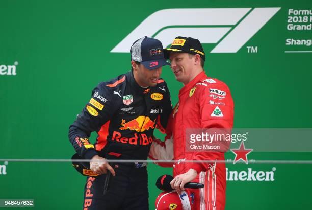 Race winner Daniel Ricciardo of Australia and Red Bull Racing talks with third place finisher Kimi Raikkonen of Finland and Ferrari on the podium...