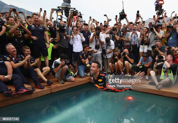 Race winner Daniel Ricciardo of Australia and Red Bull Racing celebrates with a swan dive into the swimming pool of the Red Bull Energy Station after...