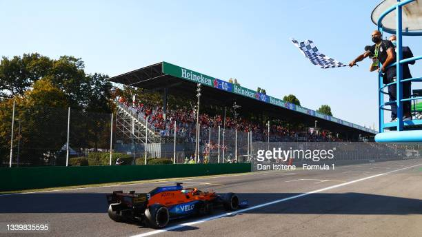 Race winner Daniel Ricciardo of Australia driving the McLaren F1 Team MCL35M Mercedes takes the chequered flag waved by Olympic 100m champion Lamont...