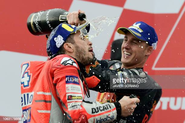 Race winner Ducati Team's Italian rider Andrea Dovizioso celebrates on the podium with third placed Red Bull KTM Factory Racing's Spanish rider Pol...