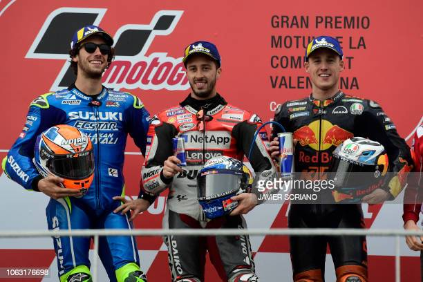 Race winner Ducati Team's Italian rider Andrea Dovizioso celebrates on the podium with second placed Team SUZUKI ECSTAR's Spanish rider Alex Rins and...