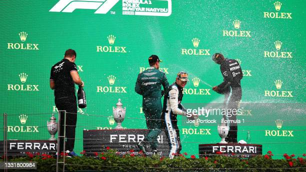 Race winner Esteban Ocon of France and Alpine F1 Team, second placed Sebastian Vettel of Germany and Aston Martin F1 Team and third placed Lewis...