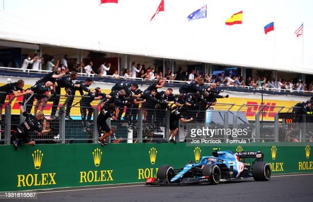 Race winner Esteban Ocon of France driving the Alpine A521 Renault passes his team celebrating on the pitwall during the F1 Grand Prix of Hungary at...