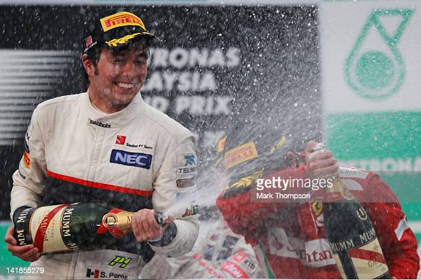 Race winner Fernando Alonso of Spain and Ferrari and second placed Sergio Perez of Mexico and Sauber F1 celebrate on the podium following the...