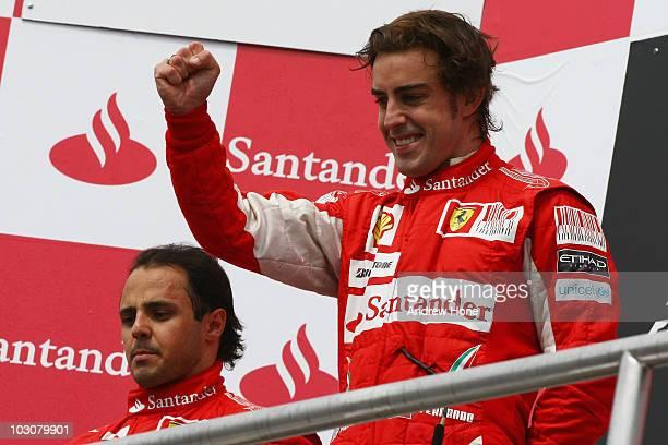 Race winner Fernando Alonso of Spain and Ferrari celebrates on the podium alongside second placed team mate Felipe Massa of Brazil and Ferrari after...