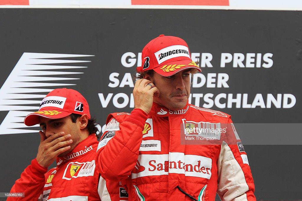 Race winner Fernando Alonso (R) of Spain and Ferrari celebrates on the podium with second placed Felipe Massa (L) of Brazil and Ferrari following the German Grand Prix at Hockenheimring on July 25, 2010 in Hockenheim, Germany.