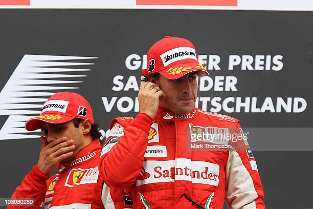 Race winner Fernando Alonso of Spain and Ferrari celebrates on the podium with second placed Felipe Massa of Brazil and Ferrari following the German...
