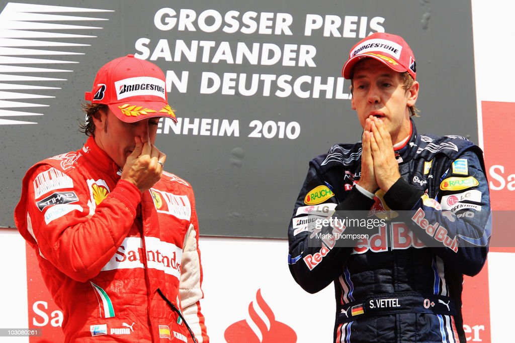 Race winner Fernando Alonso (L) of Spain and Ferrari celebrates on the podium with third placed Sebastian Vettel (R) of Germany and Red Bull Racing following the German Grand Prix at Hockenheimring on July 25, 2010 in Hockenheim, Germany.
