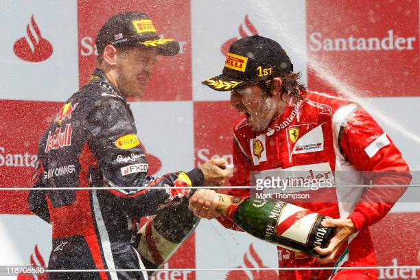 Race winner Fernando Alonso of Spain and Ferrari celebrates on the podium with second placed Sebastian Vettel of Germany and Red Bull Racing...