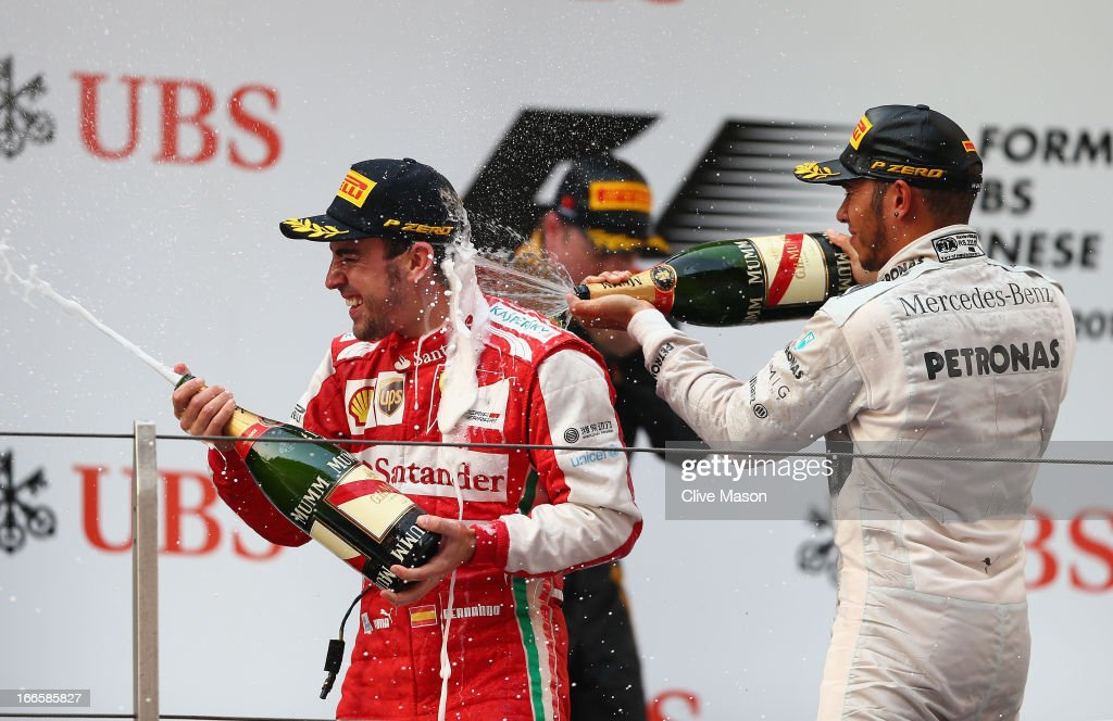 Race winner Fernando Alonso (L) of Spain and Ferrari celebrates on the podium with third placed Lewis Hamilton (R) of Great Britain and Mercedes GP following the Chinese Formula One Grand Prix at the Shanghai International Circuit on April 14, 2013 in Shanghai, China.