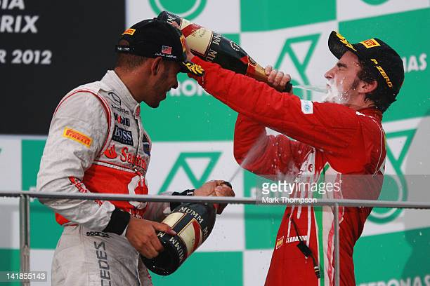 Race winner Fernando Alonso of Spain and Ferrari celebrates with third placed Lewis Hamilton of Great Britain and McLaren on the podium after winning...