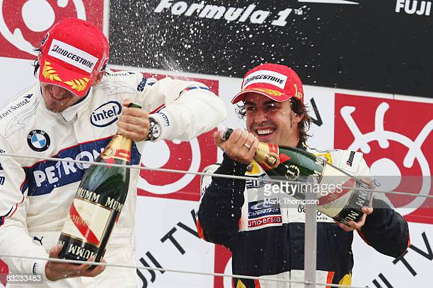 Race winner Fernando Alonso of Spain and Renault celebrates on the podium with second placed Robert Kubica of Poland and BMW Sauber following...