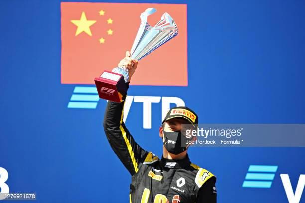 Race winner Guanyu Zhou of China and UNI-Virtuosi Racing celebrates on the podium during the Formula 2 Championship Sprint Race at Sochi Autodrom on...