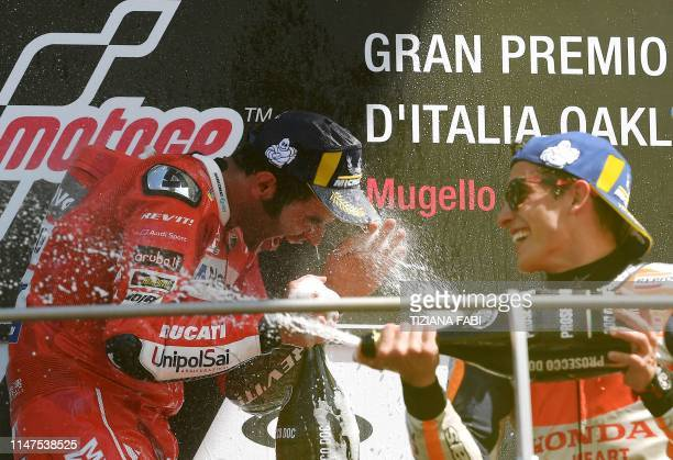 Race winner Italy's Danilo Petrucci and runnerup Spain's Marc Marquez spray champagne as they celebrate on the podium after the Italian Moto GP Grand...