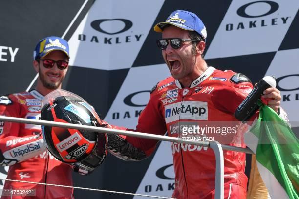 Race winner Italy's Danilo Petrucci celebrates on the podium next to thirdplaced Italy's Andrea Dovizioso after the Italian Moto GP Grand Prix at the...