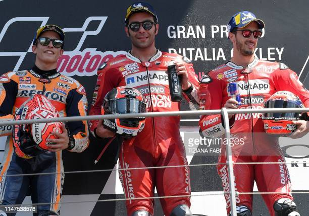 Race winner Italy's Danilo Petrucci celebrates on the podium with runnerup Spain's Marc Marquez and thirdplaced Italy's Andrea Dovizioso after the...