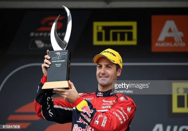 Race winner Jamie Whincup driver of the Red Bull Holden Racing Team Holden Commodore VF holds the Jason Richards memorial trophy aloft after race 24...