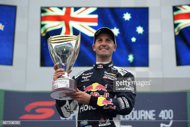 Race winner Jamie Whincup driver of the Red Bull Holden Racing Team Holden Commodore ZB celebrates on the podium during race 2 for the Supercars...