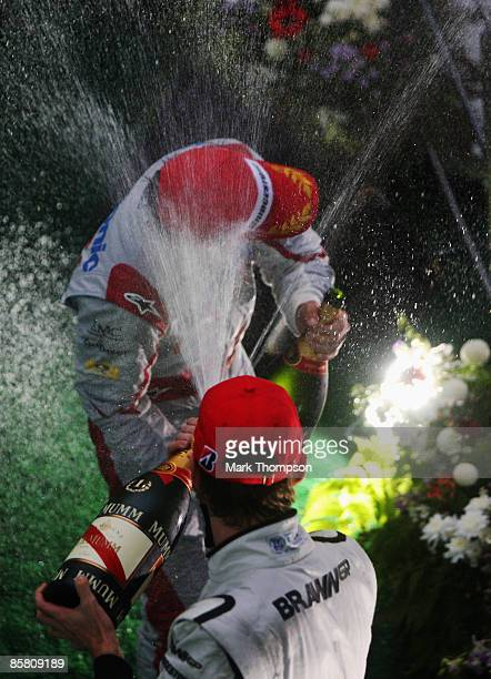Race winner Jenson Button of Great Britain and Brawn GP and third placed Timo Glock of Germany and Toyota celebrate on the podium following the rain...