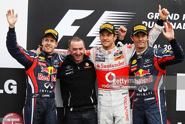 Race winner Jenson Button of Great Britain and McLaren celebrates on the podium with third placed Mark Webber of Australia and Red Bull Racing,...