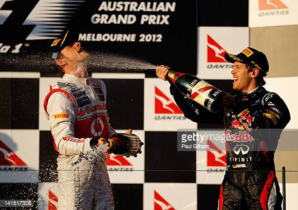 Race winner Jenson Button of Great Britain and McLaren celebrates with second placed Sebastian Vettel of Germany and Red Bull Racing on the podium...