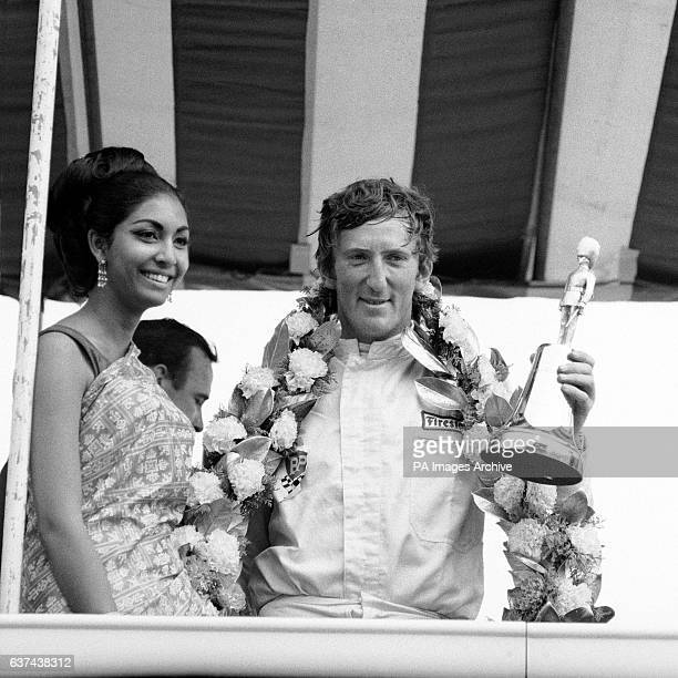 Race winner Jochen Rindt holds up his trophy after being presented with it by Miss World 1966, Reita Faria