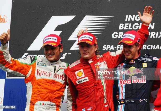 Race winner Kimi Raikkonen of Finland and Ferrari celebrates on the podium with second placed Giancarlo Fisichella of Italy and Force India and third...