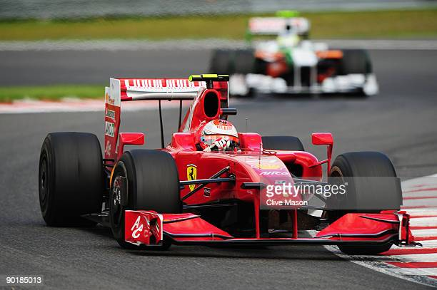 Race winner Kimi Raikkonen of Finland and Ferrari leads from second placed Giancarlo Fisichella of Italy and Force India during the Belgian Grand...