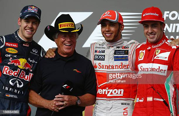 Race winner Lewis Hamilton of Great Britain and McLaren appears on the podium with second placed Sebastian Vettel of Germany and Red Bull Racing,...