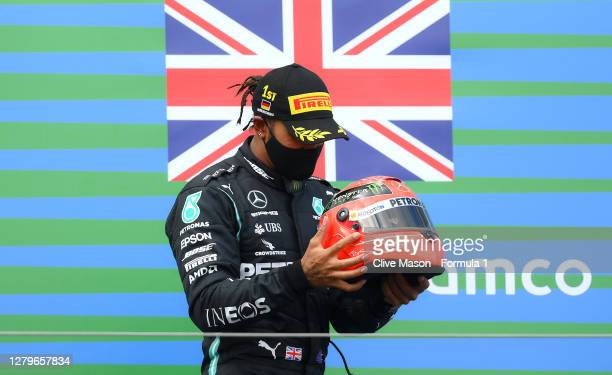 Race winner Lewis Hamilton of Great Britain and Mercedes GP celebrates after being presented with a helmet of Michael Schumacher for matching his...