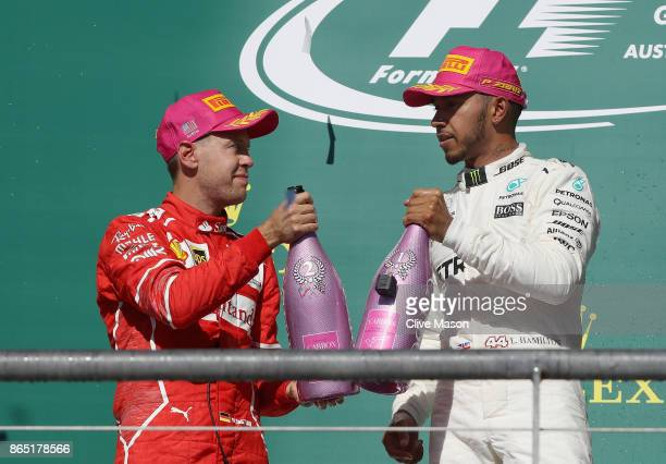 Race winner Lewis Hamilton of Great Britain and Mercedes GP and second place finisher Sebastian Vettel of Germany and Ferrari on the podium during...
