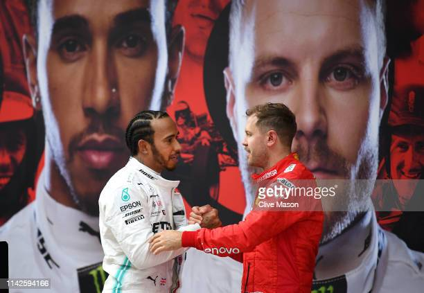 Race winner Lewis Hamilton of Great Britain and Mercedes GP and third placed finisher Sebastian Vettel of Germany and Ferrari in parc ferme during...
