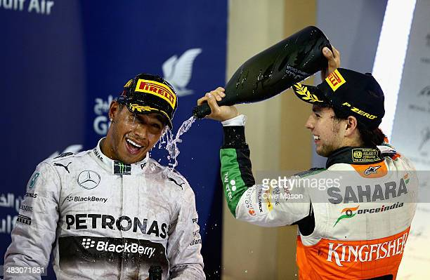 Race winner Lewis Hamilton of Great Britain and Mercedes GP and third placed Sergio Perez of Mexico and Force India celebrate on the podium following...
