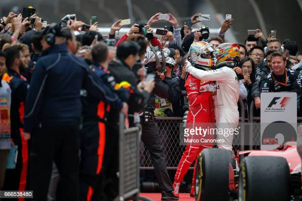 Race winner Lewis Hamilton of Great Britain and Mercedes GP embraces second placed finisher Sebastian Vettel of Germany and Ferrari in parc ferme...