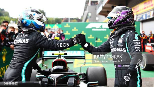 Race winner Lewis Hamilton of Great Britain and Mercedes GP fist bumps second placed Valtteri Bottas of Finland and Mercedes GP in parc ferme during...