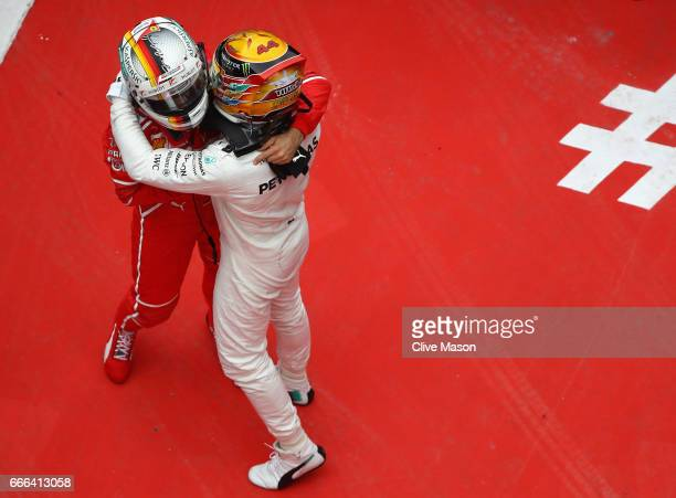 Race winner Lewis Hamilton of Great Britain and Mercedes GP hugs second placed finisher Sebastian Vettel of Germany and Ferrari in parc ferme during...