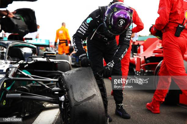 Race winner Lewis Hamilton of Great Britain and Mercedes GP inspects his punctured tyre in parc ferme during the F1 Grand Prix of Great Britain at...