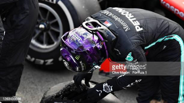 Race winner Lewis Hamilton of Great Britain and Mercedes GP inspects his tyre in parc ferme after getting a puncture on the last lap during the F1...