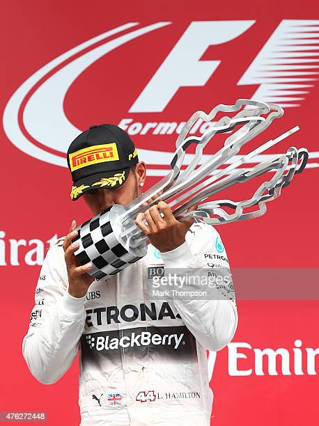 Race winner Lewis Hamilton of Great Britain and Mercedes GP kisses the trophy on the podium during the Canadian Formula One Grand Prix at Circuit...