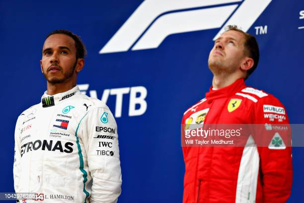 Race winner Lewis Hamilton of Great Britain and Mercedes GP looks on as third placed Sebastian Vettel of Germany and Ferrari looks dejected on the...