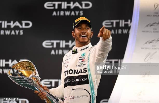 Race winner Lewis Hamilton of Great Britain and Mercedes GP celebrates on the podium during the F1 Grand Prix of Abu Dhabi at Yas Marina Circuit on...