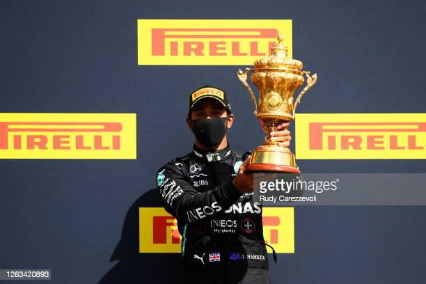 Race winner Lewis Hamilton of Great Britain and Mercedes GP celebrates on the podium during the F1 Grand Prix of Great Britain at Silverstone on...