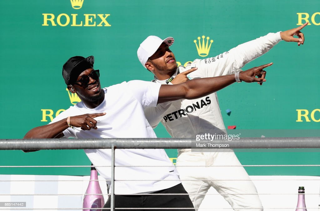 Race winner Lewis Hamilton of Great Britain and Mercedes GP celebrates on the podium with sprinting legend Usain Bolt during the United States Formula One Grand Prix at Circuit of The Americas on October 22, 2017 in Austin, Texas.