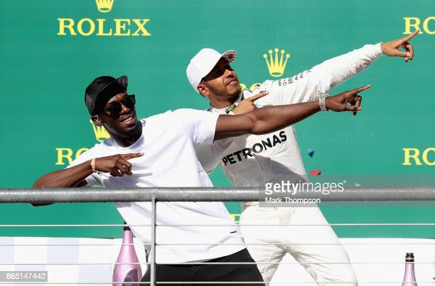 Race winner Lewis Hamilton of Great Britain and Mercedes GP celebrates on the podium with sprinting legend Usain Bolt during the United States...