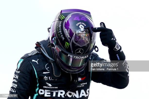 Race winner Lewis Hamilton of Great Britain and Mercedes GP points to the 'Black Lives Matter' symbol on his helmet as he celebrates in parc ferme...