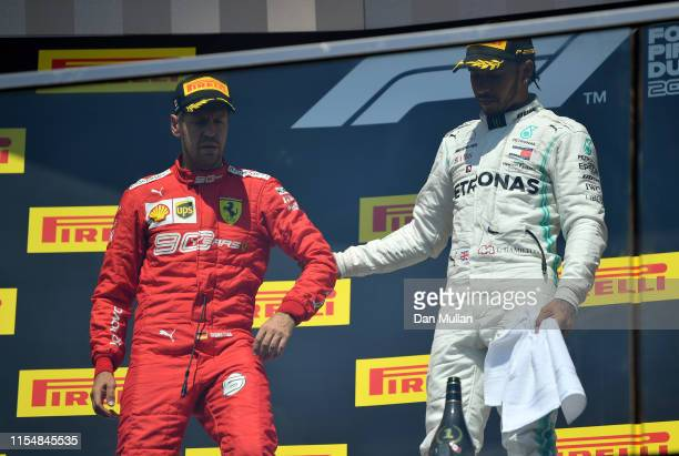 Race winner Lewis Hamilton of Great Britain and Mercedes GP pulls second placed Sebastian Vettel of Germany and Ferrari onto the top step of the...