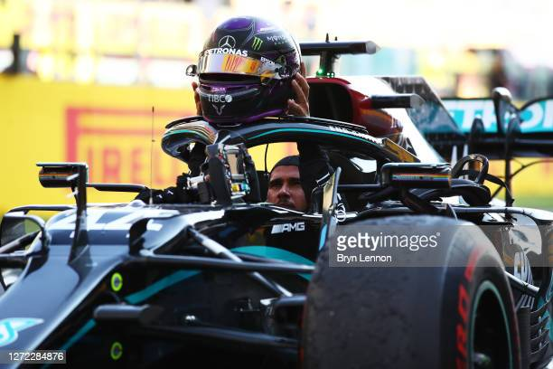 Race winner Lewis Hamilton of Great Britain and Mercedes GP removes his helmet as he climbs out of his car during the F1 Grand Prix of Tuscany at...