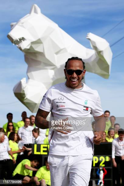 Race winner Lewis Hamilton of Great Britain and Mercedes GP runs from his team as they spray champagne at the celebrations after the F1 Grand Prix of...